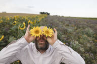 Playful man covering his eyes with sunflowers in a field - KMKF01058