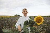 Portrait of a happy boy holding a sunflower in a field - KMKF01067