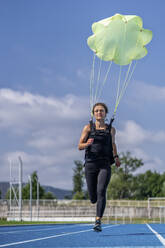 Female runner with parachute on tartan track - STSF02202