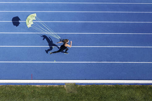 Top view of female runner with parachute on tartan track - STSF02205