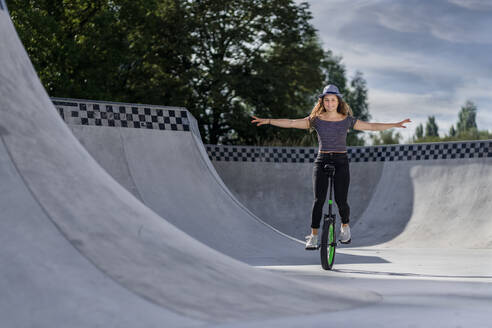 Young woman riding unicycle in skatepark - STSF02211