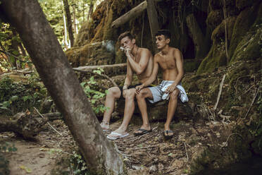 Two barechested friends smoking a joint of marijuana in nature - ACPF00628