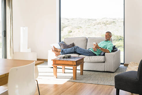 Senior man using cell phone on couch at home - SBOF01981