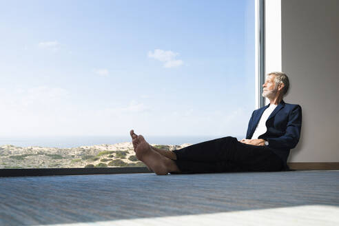 Senior businessman sitting at panorama window looking out - SBOF01999