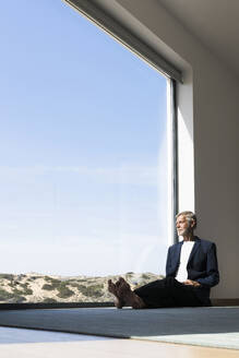 Senior businessman sitting at panorama window looking out - SBOF02002