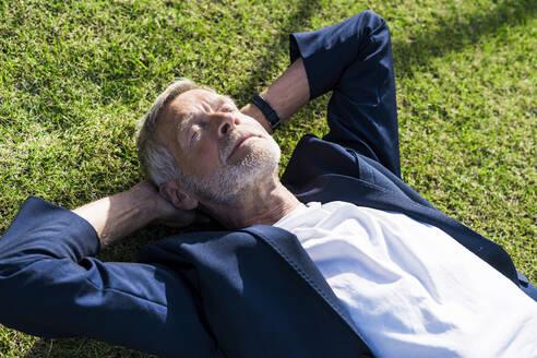 Senior businessman lying in grass with closed eyes - SBOF02026