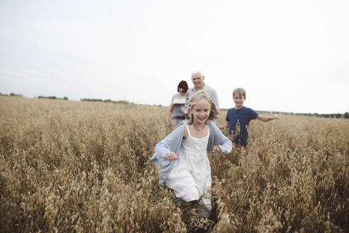 Portrait of happy girl running in an oat field while brother, grandmother and grandfather following her - EYAF00413