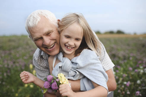 Portrait of happy grandfather and granddaughter with picked flowers on a meadow - EYAF00425