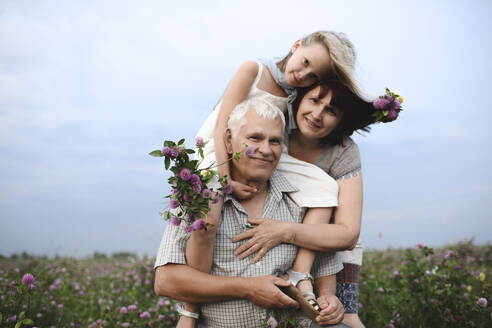 Portrait of little girl and her grandparents with picked flowers in nature - EYAF00428
