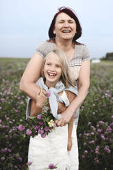 Portrait of laughing grandmother and granddaughter with pickes flowers on a meadow - EYAF00431