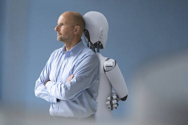 Businessman standing back to back with robot - KSHSF00004