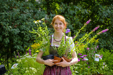 Portrait of redheaded teenage girl holding plants in garden - LBF02693
