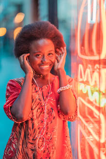 Smiling young woman with headphones standing next to neon light - DLTSF00006