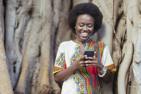 Laughing young woman leaning on a tree trunk using her smartphone - DLTSF00020