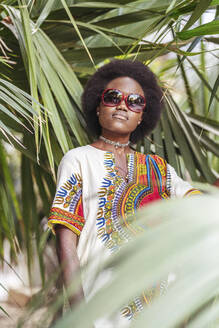 Cool young woman wearing sunglasses posing among tropical plants - DLTSF00023
