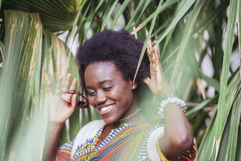 Smiling young woman standing among tropical plants - DLTSF00029