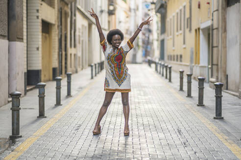 Happy young woman standing with arms outstretched in the middle of a street - DLTSF00038