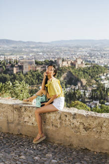 Young woman with camera sitting on a wall at the Alhambra, Granada, Spain - LJF00957