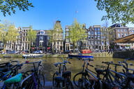 Bicycles parked on the banks of the river Amstel and typical houses, Amsterdam, Holland (The Netherlands), Europe - RHPLF07775