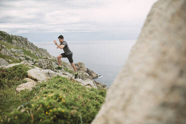 Trail runner in coastal landscape, Ferrol, Spain - RAEF02280