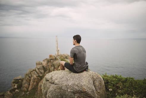 Trail runner sitting on a rock in coastal landscape, Ferrol, Spain - RAEF02286