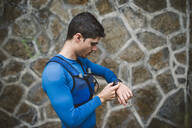 Trail runner standing at a wall looking at his smartwatch - RAEF02298