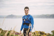 Portrait of smiling trail runner standing in the mountains, Ferrol, Spain - RAEF02301