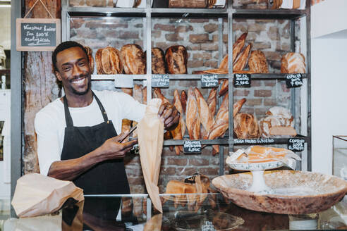 Smiling man working in a bakery - JCMF00147