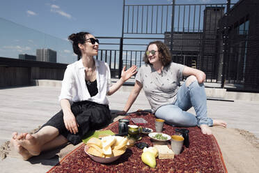 Woman with below-elbow amputation with her friend having a healthy meal on the roof - EYAF00454