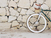 Fixie bike leaning against natural stone wall, partial view - DLTSF00044