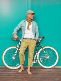 Barefoot man with Fixie bike standing in front of green wall - DLTSF00053