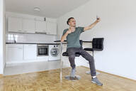 Young man taking a selfie with his smartphone in an empty apartment - FLLF00285