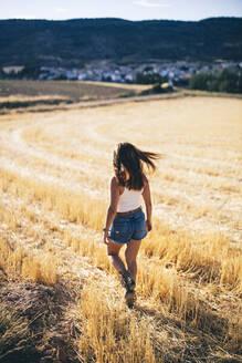 Rear view of woman, walking in field - OCMF00596