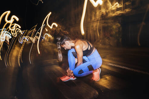 Athlete tying shoe laces in the street at night - JCMF00156