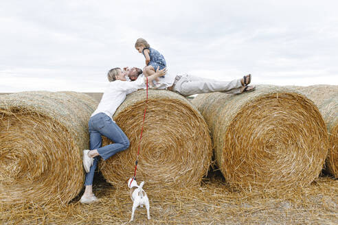 Happy family with dog embracing on hay bales - KMKF01073