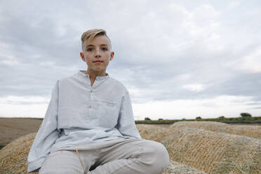Portrait of blond boy, sitting on a hay bale - KMKF01076