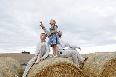 Father and his children sitting on hay bales, watching sky - KMKF01079