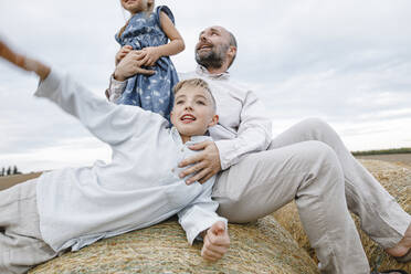 Father and his children playing and laughing on hay bales - KMKF01082