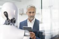 Businessman using digital device to control robot - KSHSF00017