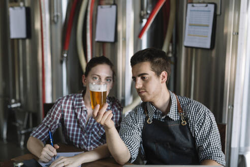 Young entrepreneurs working at a brewery testing beer - ALBF01058