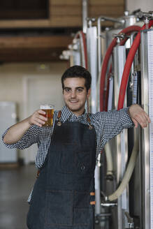 Portrait of confident young man holding beer glass at a brewery - ALBF01076