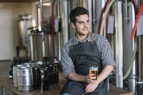 Young man drinking a beer at a brewery - ALBF01097