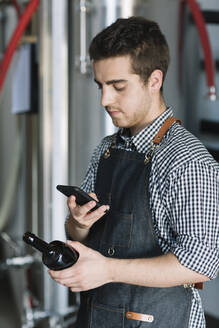 Young man holding smartphone and beer bottle at a brewery - ALBF01100
