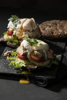 Close-up of open faced sandwich on table against black background - MAEF12930