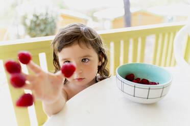 Cute little girl with raspberries on her fingertips - GEMF03125