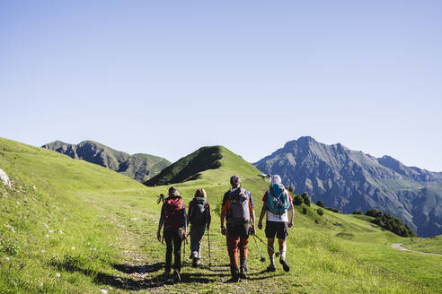 Group of hikers walking in the mountains, Orobie Mountains, Lecco, Italy - MCVF00002