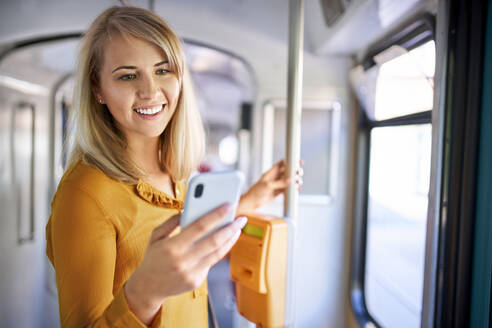 Smiling young woman using smartphone in a tram - BSZF01331