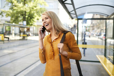 Happy young woman on the phone at tram stop - BSZF01334