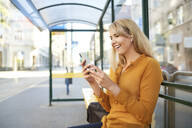 Happy young woman with wireless earphones using smartphone at bus stop - BSZF01337