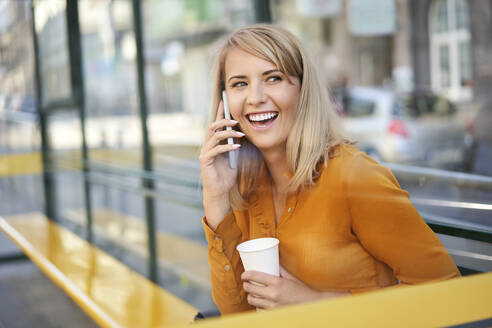 Happy young woman with smartphone and takeaway coffee at bus stop - BSZF01340